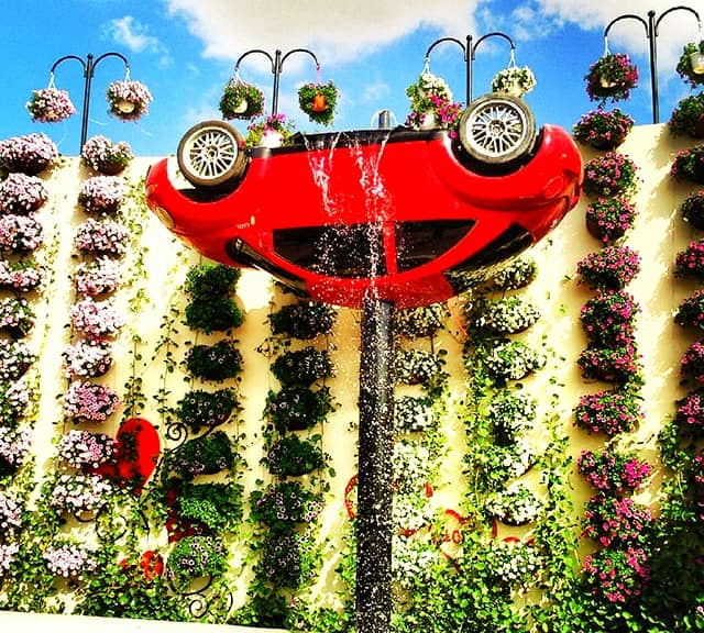 An Upside-down version of inverted Volkswagen Car with a waterfall at the Dubai Miracle Garden.